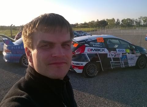 Photo of Hannes Tõnisson in front of a rally car